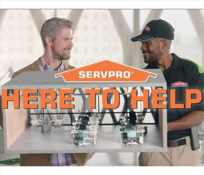 "SERVPRO employee and man talking with ""HERE TO HELP"""
