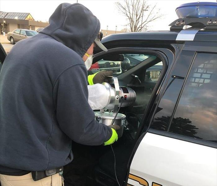 SERVPRO employee disinfecting police car