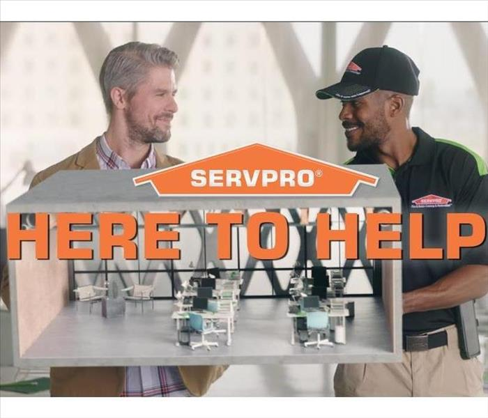 "SERVPRO employee talking to business owner with ""Here to Help"""